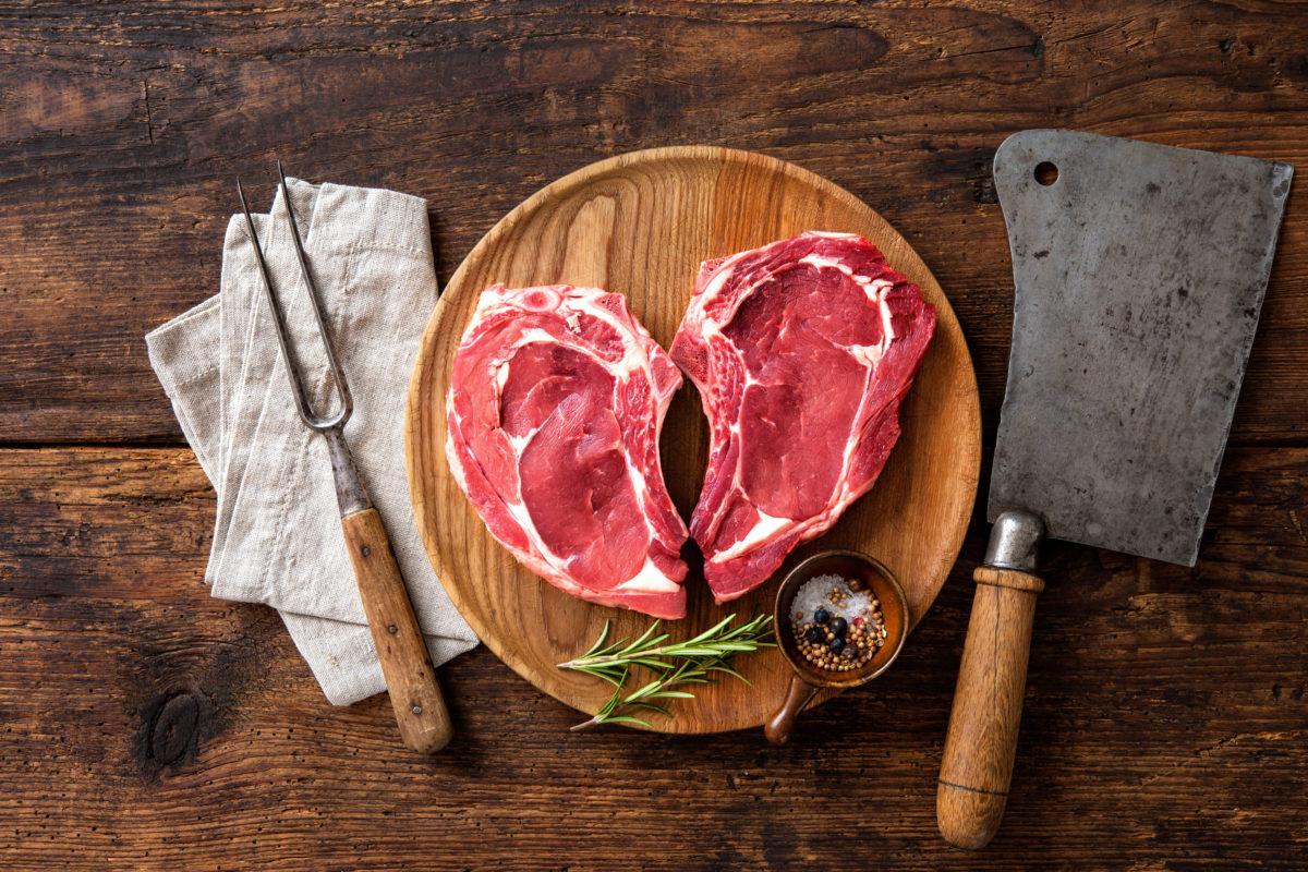 Fleisch in Form eines Herz mit Kräutern und Holzuntergrund und Metzgerbesteck
