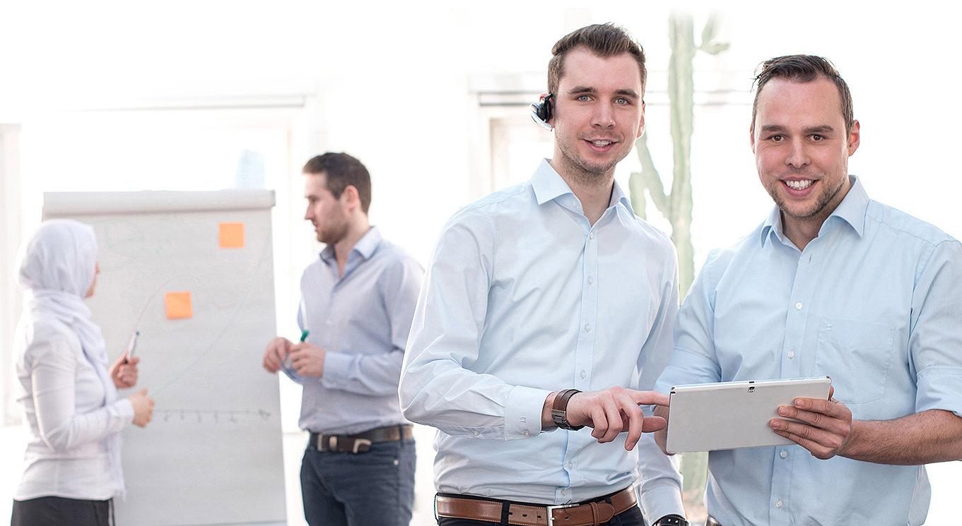 IT Beratung KiRa, 2 Männer im Vordergrund mit Tablet und 2 Kollegen im Hintergrund an einem Flipchart