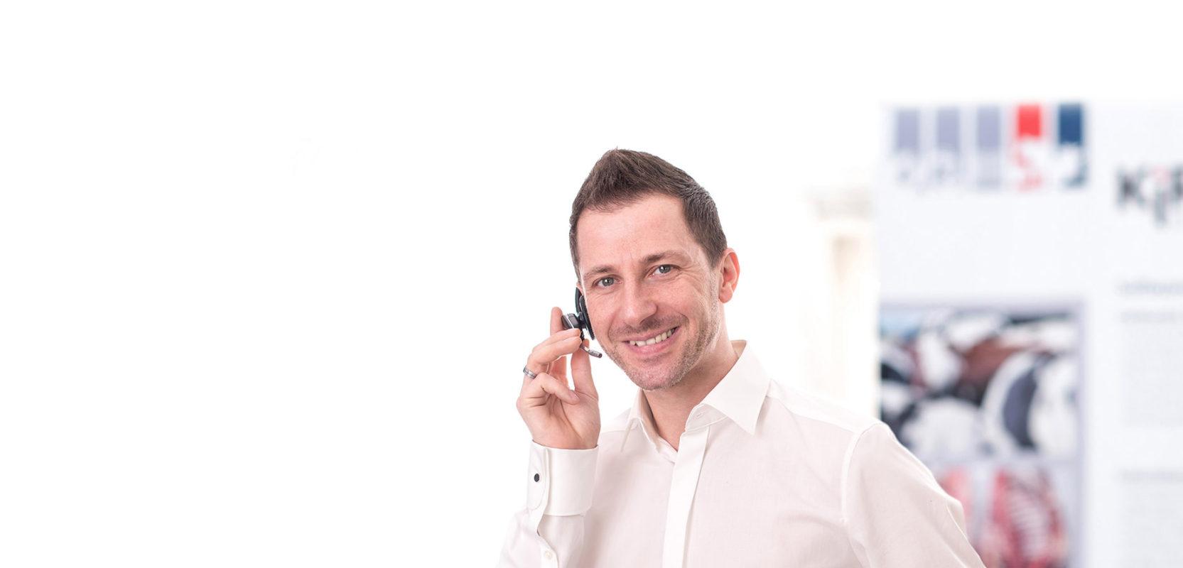 IT-Support KiRa, Mann hat Headset auf und KiRa Logo im Hintergrund