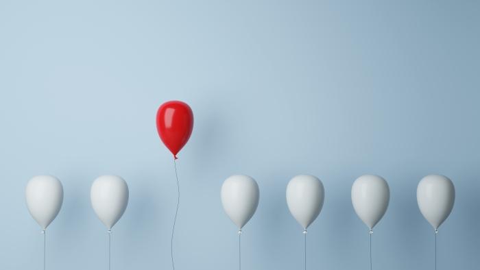 Von der Masse absetzen als Konzept mit einem roten Luftballon