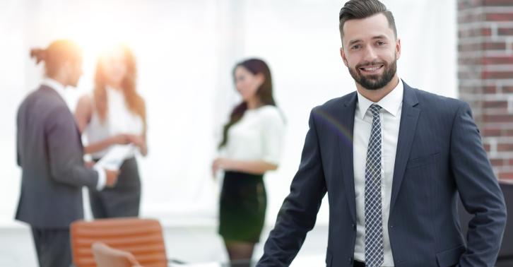 portrait of a smiling businessman on the background of the workplace